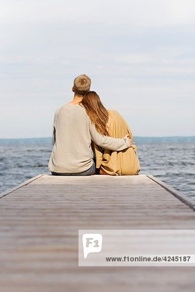 Back view of a young couple sitting in a pier