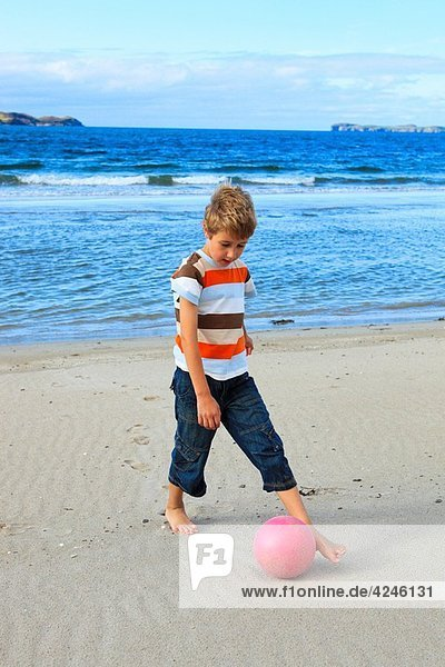 boy playing football on beach  Sutherland  Scotland