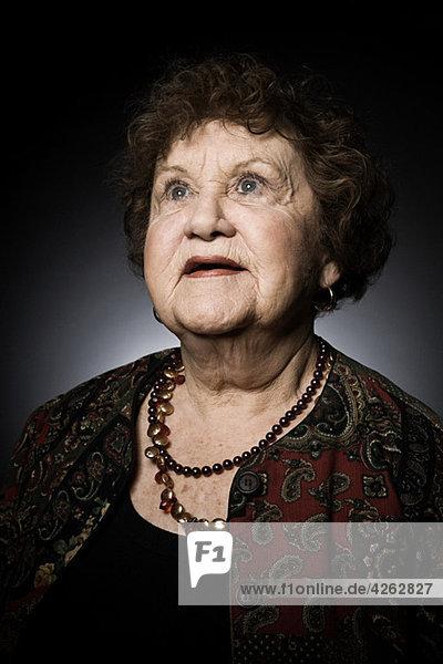 Studio-Porträt einer älteren Frau  die nach oben schaut