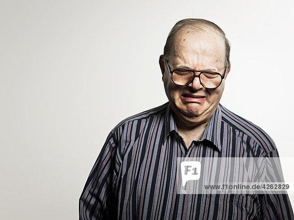 Studio-Porträt eines traurigen älteren Mannes  der weint