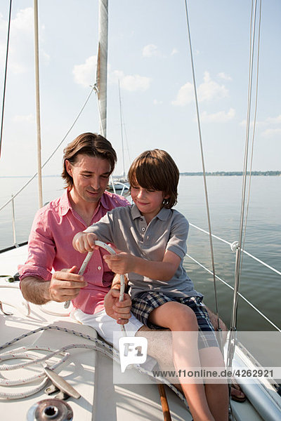 Father and son on board yacht with rope