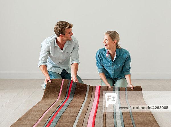 Junges Paar  das den Teppich auf dem Boden abrollt