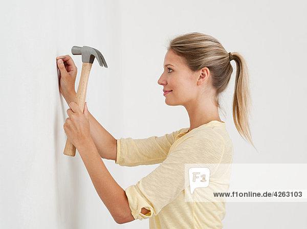 Junge Frau schlägt Nagel in die Wand