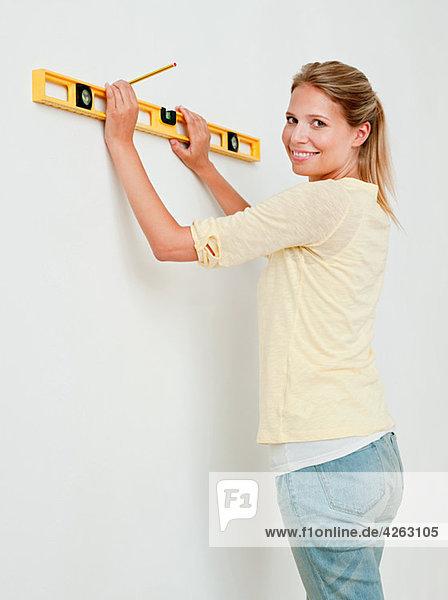 Junge Frau mit Wasserwaage an der Wand