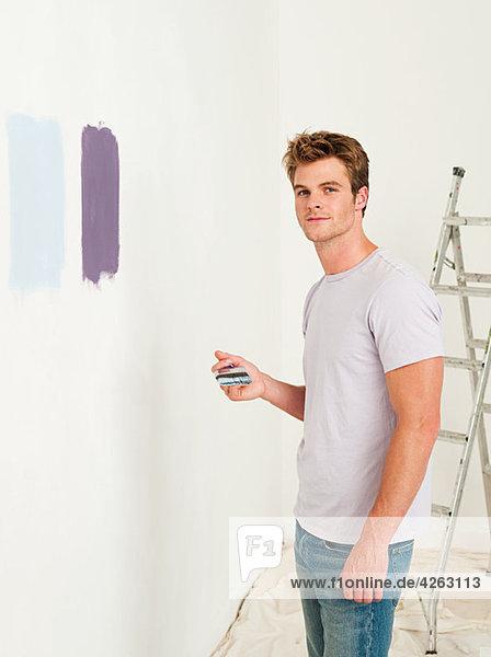 Junger Mann mit Farbe an der Wand