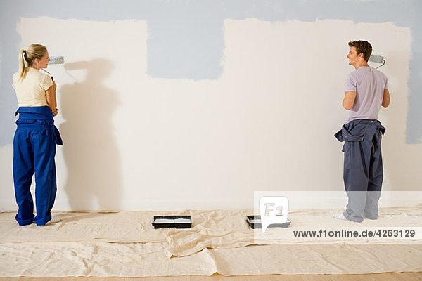 Junges Paar malt Wand