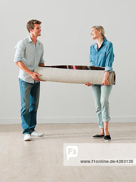 Junges Paar mit aufgerolltem Teppich