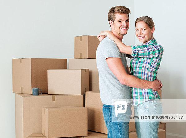 Junges Paar umarmt von Pappkartons