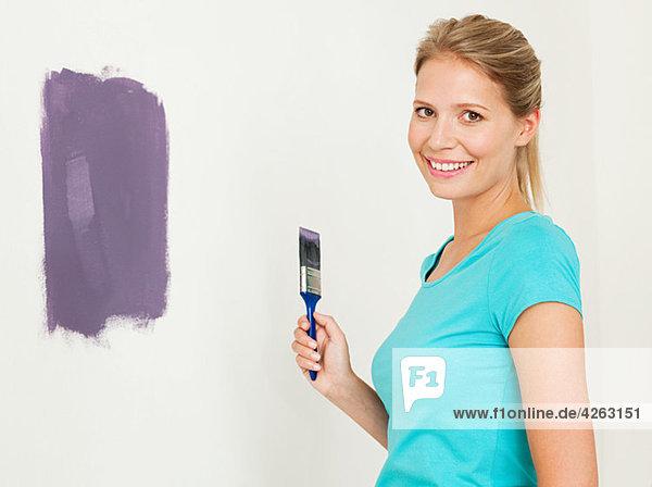Junge Frau beim Malen einer Wand
