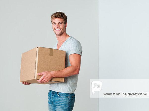 Junger Mann mit Kartonschachtel