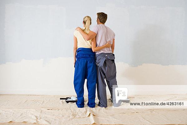 Rückansicht des Paares beim Betrachten der Farbe an der Wand