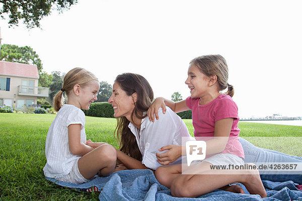 Glückliche Mutter und Töchter auf Gras liegend