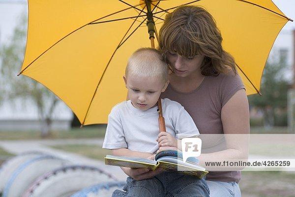 Junge und Frau sitzen unter yellow Umbrella ein Buch zu lesen