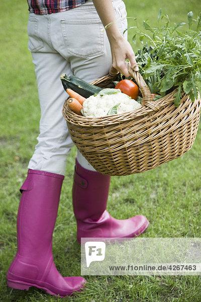 junge Frau mit Korb mit Gemüse