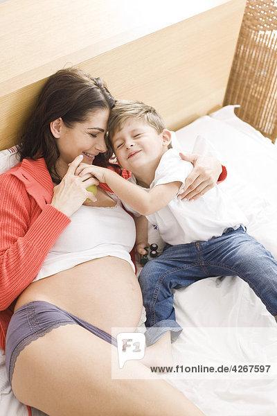 Schwangere Frau spielen mit Sohn im Bett