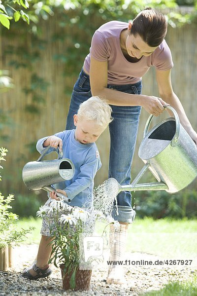 Mutter mit Kleinkind Bewässerung von Pflanzen im Garten