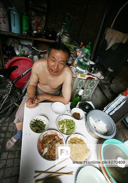 Man eating in his house  Old Town  Hutong  Beijing  China