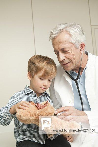 Junge mit Teddybär beim Arzt