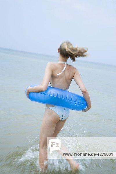 fröhliche Frau spielen im Meer