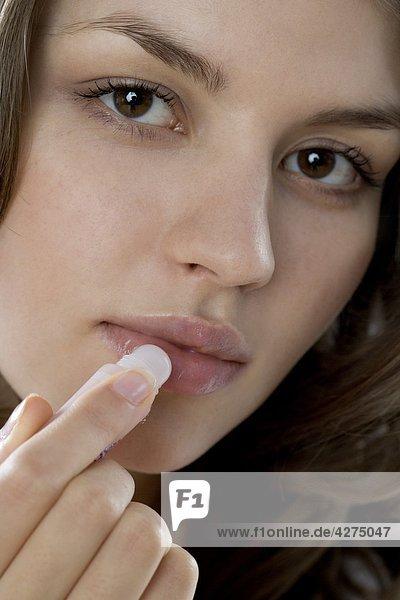 Young Frau trägt Lippenbalsam auf