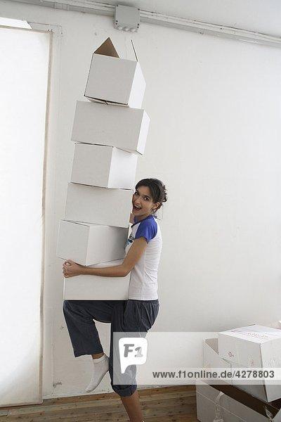 Junge Frau nimmt einen Stapel von Papierschachteln