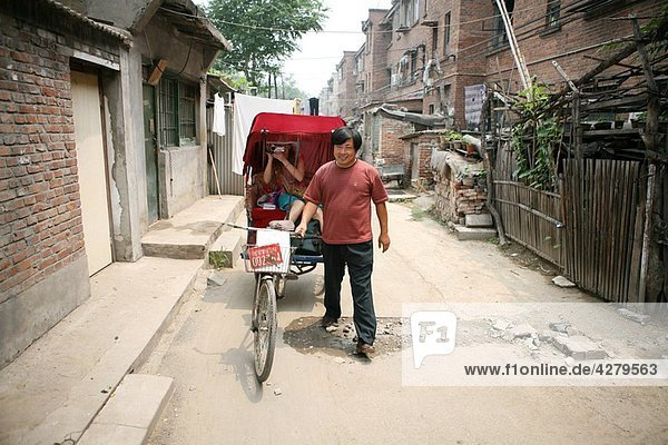 Tourist riding in cycle rickshaw  Hutong District  Beijing  China  Asia
