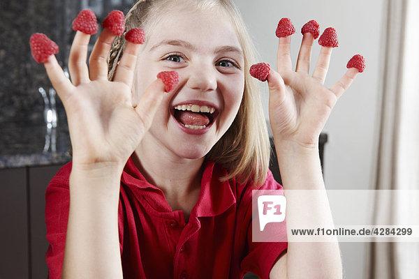 Mädchen mit Himbeeren an den Fingern
