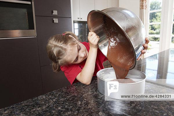 Mädchen gießen Kuchenmischung in die Kuchenform