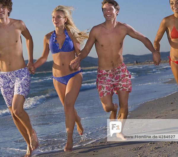 Junge Energiegruppe läuft am Strand
