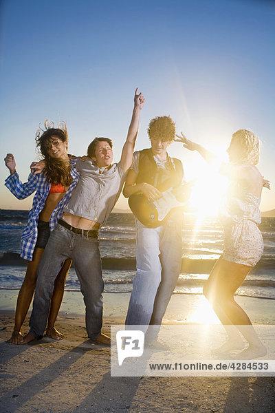 Junge Gruppe mit Gitarrentanz am Strand