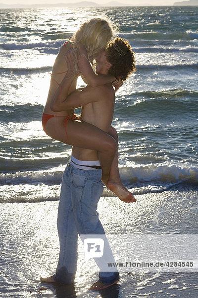Junger Kuss am Strand bei Sonnenuntergang