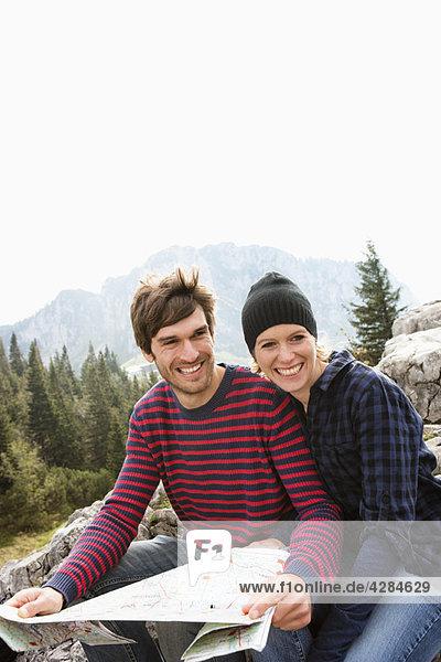 Paar mit Karte auf Felsen sitzend