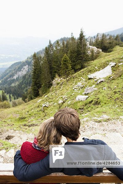 Paar sitzend auf der Bank umarmend