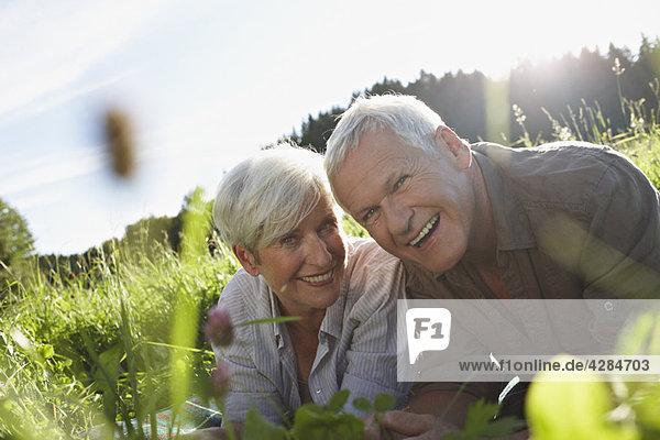 Seniorenpaar lächelnd auf den Wiesen liegend