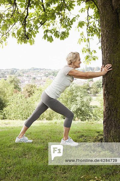 Frau streckt Bein am Baum festhaltend aus