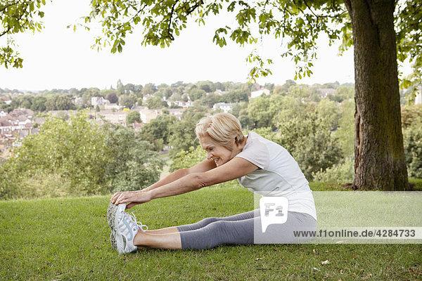 Frau streckt die Hände zu den Zehen im Park aus