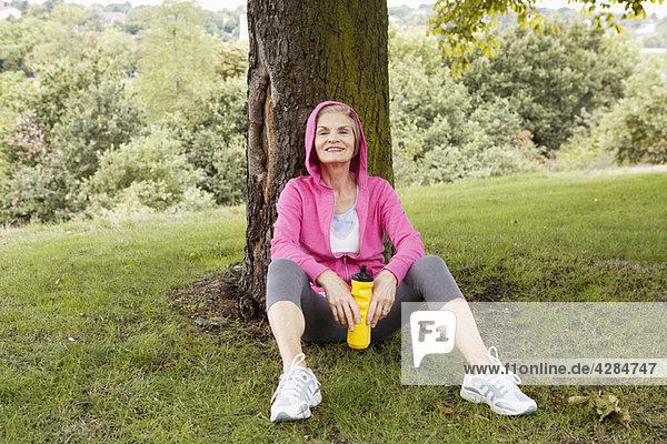 Reife Frau am Baum sitzend