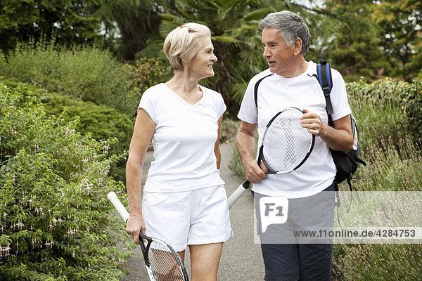 Reife Tennisspieler beim Gehen und Sprechen