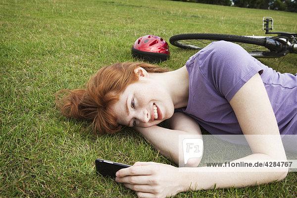 Frau im Gras liegend  textend