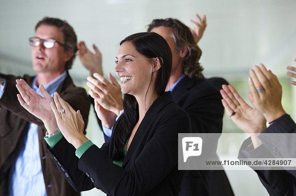 Geschäftsteam applaudiert und lächelt