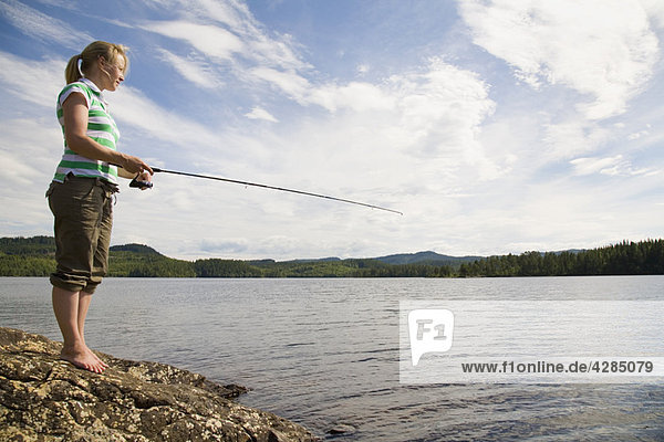 Junge Frau beim Angeln im See