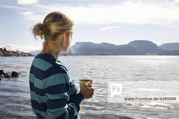 Frau mit Kaffee am Meer und in den Bergen