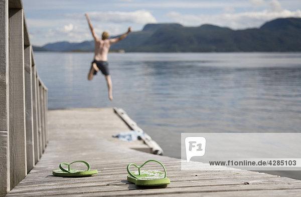 Mann springt vom Holzsteg ins Meer
