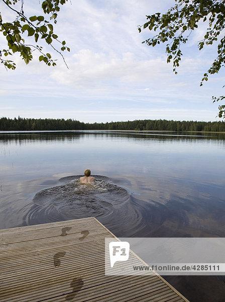 Mann schwimmt im stillen See