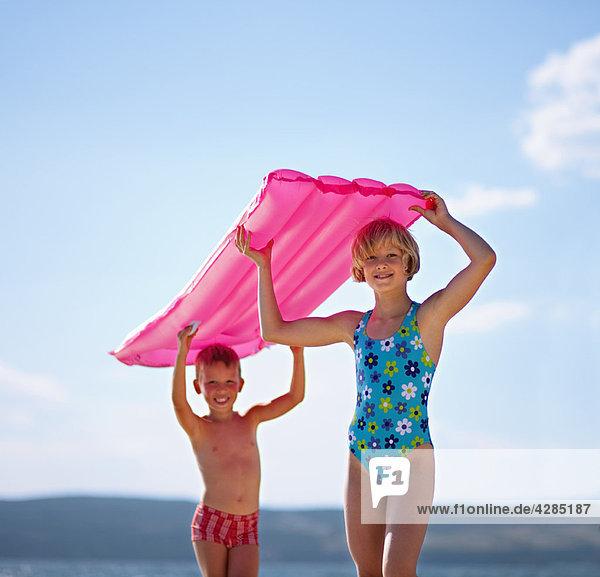 Kinder mit Schlauchboot am Strand