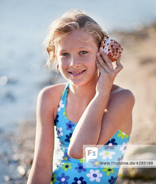 Mädchen hört Muscheln am Strand