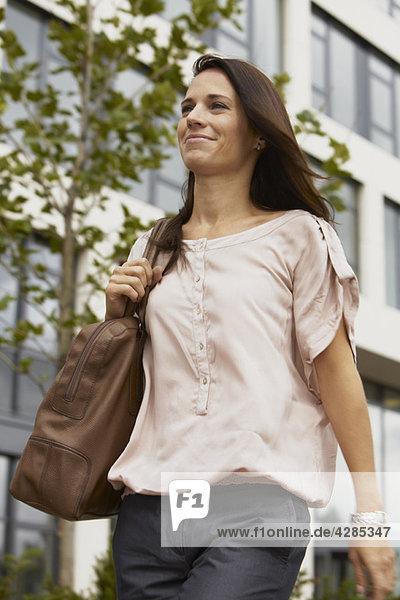 Geschäftsfrau zu Fuß  mit Geldbörse