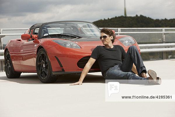 Mann sitzt vor dem Elektroauto