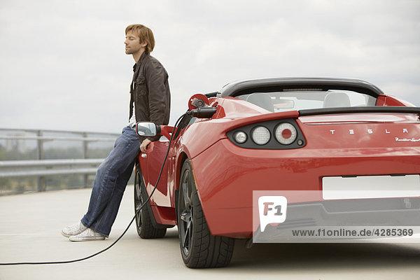 Junger Mann füllt sein Elektroauto auf