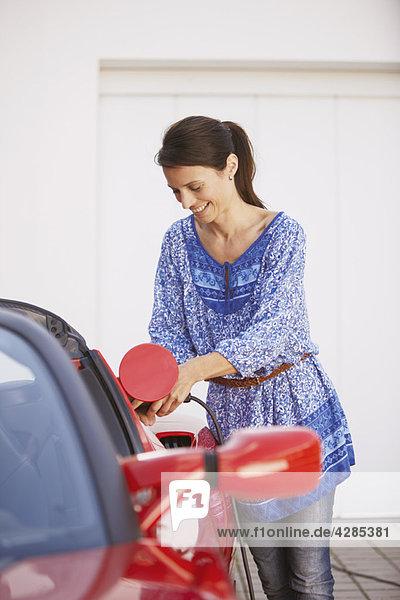 Frau beim Einstecken ihres Elektroautos